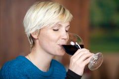 喝红葡萄酒的妇女在餐馆 库存照片