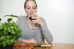 喝红葡萄酒的妇女,当烹调时 免版税库存图片