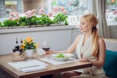喝红葡萄酒的年轻白肤金发的妇女在一家室外餐馆 库存照片