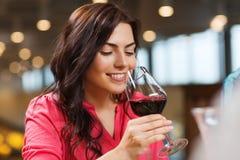 喝红葡萄酒的微笑的妇女在餐馆 免版税库存照片