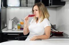 喝红葡萄酒的成功的美丽的女孩 免版税图库摄影
