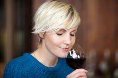 喝红葡萄酒的白肤金发的妇女在餐馆 库存照片