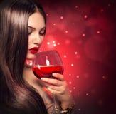 喝红葡萄酒的秀丽妇女 免版税库存图片