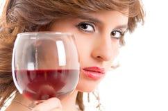 喝红葡萄酒的美丽的深色的女孩被隔绝 免版税库存照片
