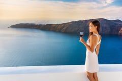 喝红葡萄酒的豪华旅馆妇女在圣托里尼 免版税库存图片
