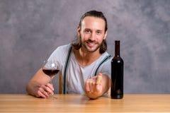 喝红葡萄酒的年轻人 免版税库存照片