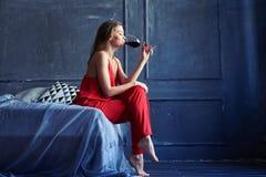 喝红葡萄酒的年轻华美的女孩,当坐床时 免版税库存照片