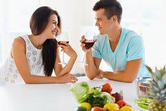 喝红葡萄酒的素食夫妇在厨房里 库存照片