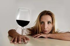 喝红葡萄酒玻璃酒瘾的白种人白肤金发的被浪费的沮丧的醺酒的妇女 图库摄影
