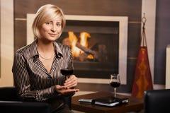 喝红葡萄酒年轻人的女实业家 库存图片