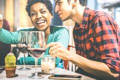 喝红酒的恋人愉快的多种族夫妇在时尚酒吧酿酒厂 免版税库存图片