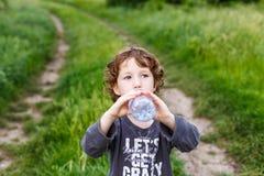 喝纯净的水本质上的孩子 逗人喜爱的卷曲小孩 库存图片