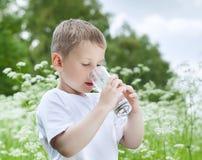 喝纯净的水的孩子 免版税库存图片