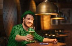 喝绿色啤酒的微笑的人在酒吧或客栈 库存照片