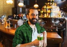 喝绿色啤酒的愉快的人在酒吧或客栈 免版税图库摄影
