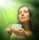 喝绿茶的美丽的妇女 免版税库存图片