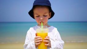 喝芒果的两年的男孩新鲜在海洋的背景的海滩 免版税库存图片