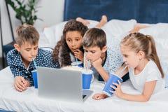喝苏打和观看电影的多文化孩子 库存图片