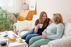 喝茶和谈话的两名妇女 母亲和女儿 免版税库存照片