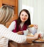 喝茶和说闲话的两名妇女 库存图片