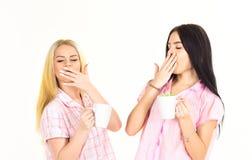 喝茶或咖啡的女孩在早晨,隔绝在白色背景 白肤金发和深色在打呵欠困的面孔 免版税库存照片
