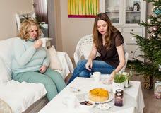 喝茶的两名妇女在圣诞树附近 有女儿的母亲 免版税库存照片