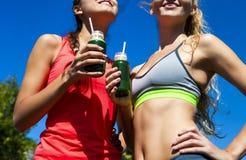 喝菜圆滑的人的两名愉快的妇女在健身runnin以后 免版税库存照片