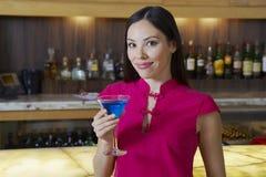 喝蓝色马蒂尼鸡尾酒的妇女 库存照片