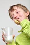 喝蛋糕的子项吃牛奶 免版税库存图片