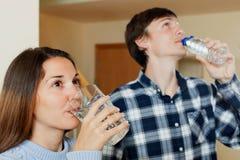 喝被装瓶的水的人和女孩 免版税库存图片