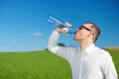 喝被装瓶的水的人 图库摄影