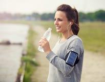 喝被装瓶的水的女性赛跑者 库存图片