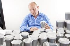 喝许多份咖啡的劳累过度的商人 免版税库存图片