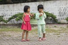 喝软饮料和使用与朋友的泰国女孩 库存照片