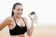 喝适合的健康水妇女年轻人的海滩 免版税库存照片