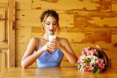 喝通过秸杆热奶咖啡的滑稽的女孩 免版税库存照片
