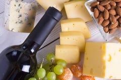 喝酒与快餐-乳酪的各种各样的类型,无花果,坚果,蜂蜜,在木板背景的葡萄 免版税库存图片