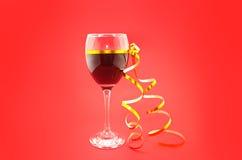 喝酒在与金黄丝带的玻璃在红色背景 免版税库存图片
