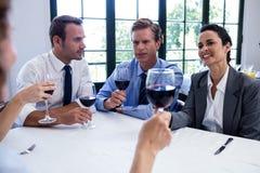 喝酒杯的小组买卖人在工作午餐会议期间 库存图片