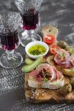 喝酒的可口开胃菜-敬酒用火腿、橄榄、蕃茄和红葡萄酒橄榄板 库存照片