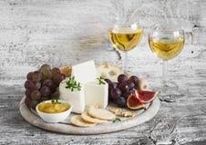 喝酒的可口开胃菜-火腿,乳酪,葡萄,薄脆饼干,无花果,坚果,果酱,在一个轻的木板和两块玻璃服务与 库存照片