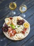 喝酒的可口开胃菜-火腿,乳酪,葡萄,薄脆饼干,无花果,坚果,果酱,在一个轻的木板和两块玻璃服务与 库存图片