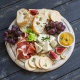 喝酒的可口开胃菜-火腿,乳酪,葡萄,薄脆饼干,无花果,坚果,果酱,在一个轻的木板服务 免版税库存照片