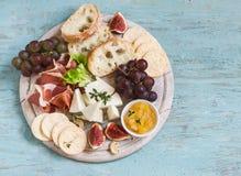 喝酒的可口开胃菜-火腿,乳酪,葡萄,薄脆饼干,无花果,坚果,果酱,在一个轻的木板服务 免版税图库摄影