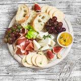 喝酒的可口开胃菜-火腿,乳酪,葡萄,薄脆饼干,无花果,坚果,果酱 库存照片