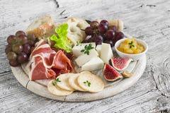 喝酒的可口开胃菜-火腿,乳酪,葡萄,薄脆饼干,无花果,坚果,果酱 免版税库存图片