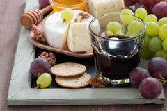 喝酒的被分类的开胃菜-乳酪、葡萄、薄脆饼干和蜂蜜 库存照片