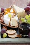喝酒的被分类的开胃菜-乳酪、葡萄、薄脆饼干和蜂蜜 免版税图库摄影