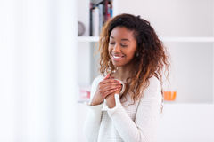 喝非裔美国人的妇女在她的客厅拿着cof 库存照片