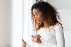 喝非裔美国人的妇女在她的客厅拿着cof 免版税库存照片